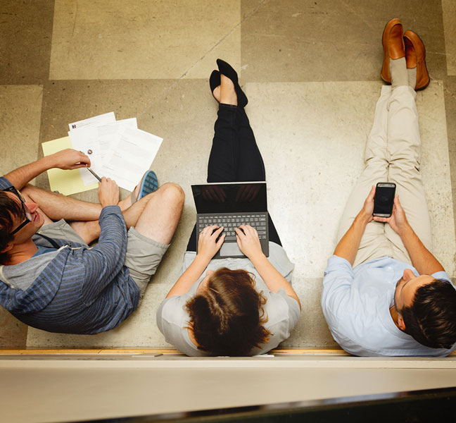 aerial view of marketing coworkers with laptop and paper on floor