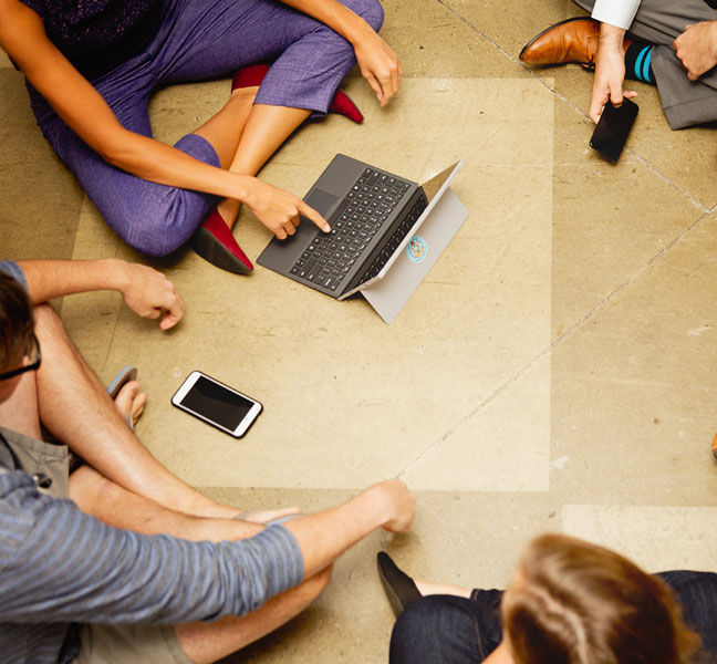 Coworkers collaborating in circle with laptop and smartphones