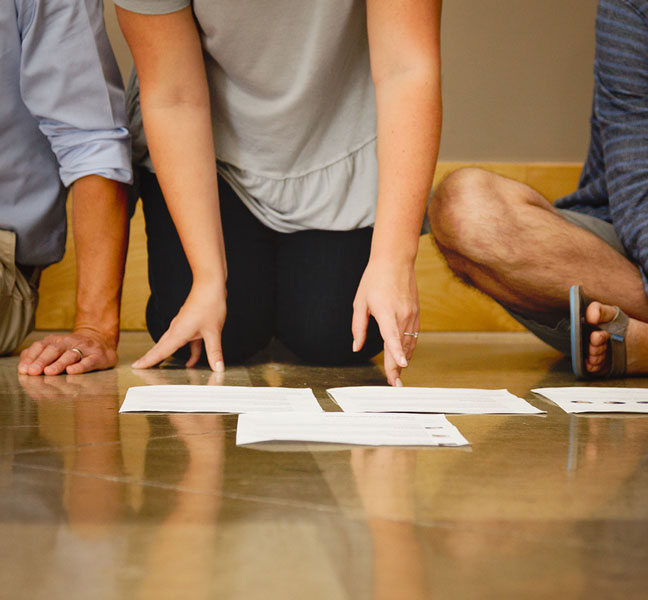 Coworkers collaborating with papers on floor